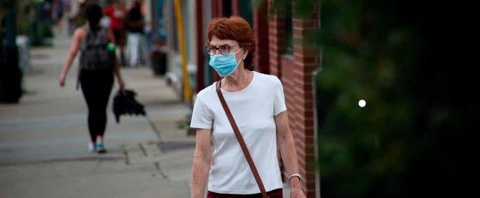 Woman walking down a street wearing mask