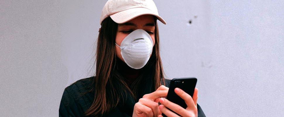 Mujer con una máscara y sosteniendo su teléfono inteligente