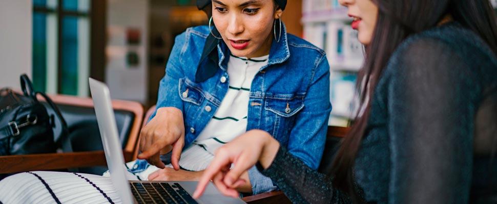 Dos mujeres trabajando con un computador.