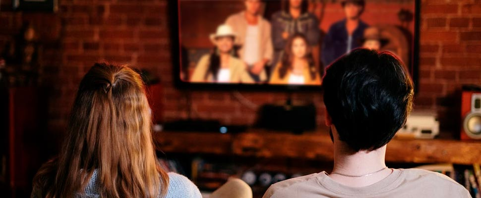 Couple watching television sitting in armchair