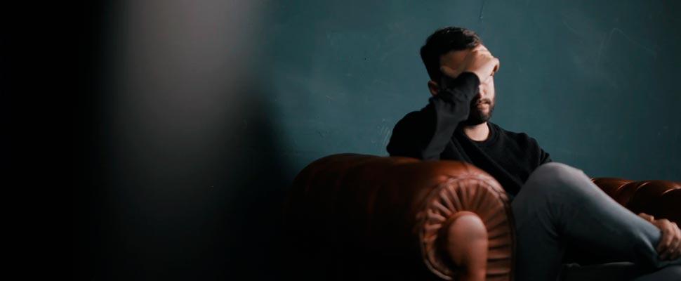 El hombre sostiene su cabeza mientras está sentado en un sofá