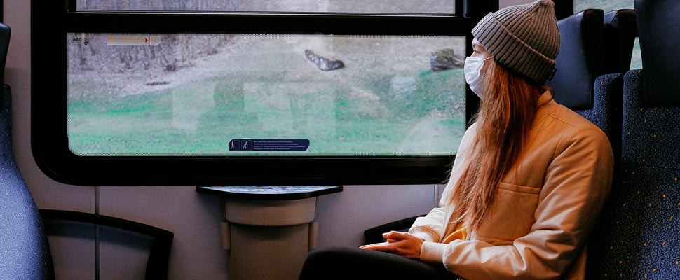 Woman wearing a mask while traveling by train.