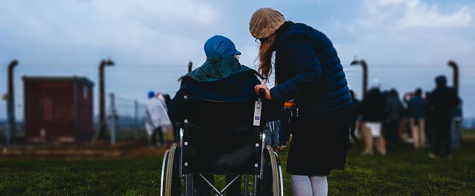 Mujer de pie al lado de una persona en silla de ruedas