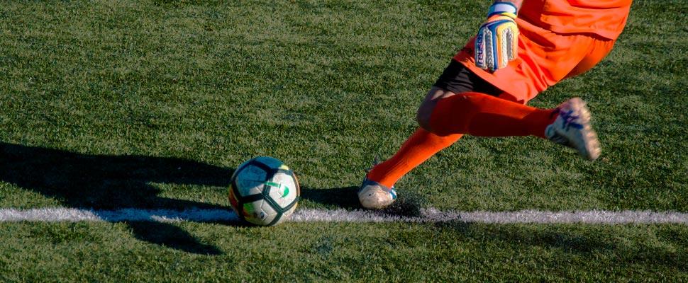 Jugador de fútbol pateando un balón