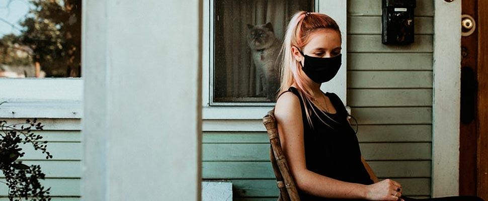 A girl in a mask sitting on her porch during the coronavirus shutdown.