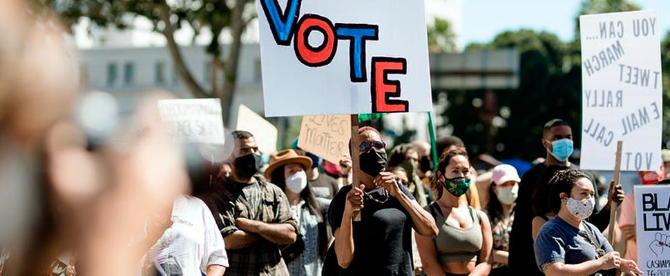 Group of protesting people with a sign that says 'Vote'