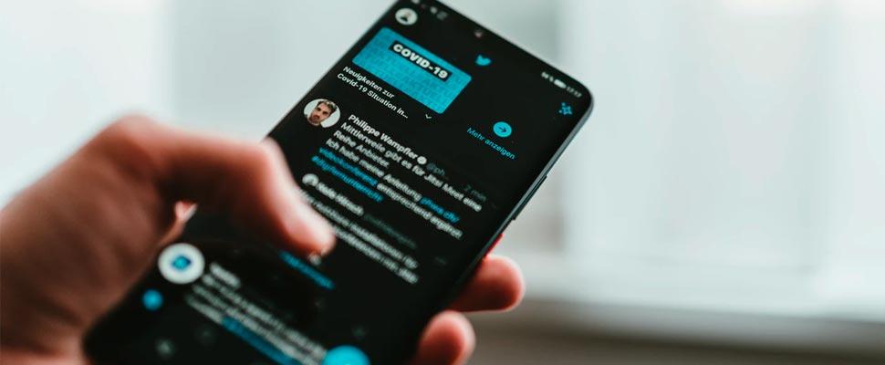 Persona holding smartphone en twitter