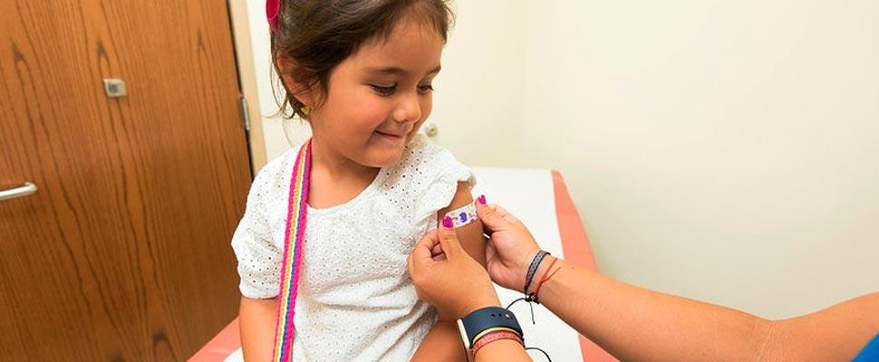 Doctor colocando un vendaje en el lugar de la inyección de un niño