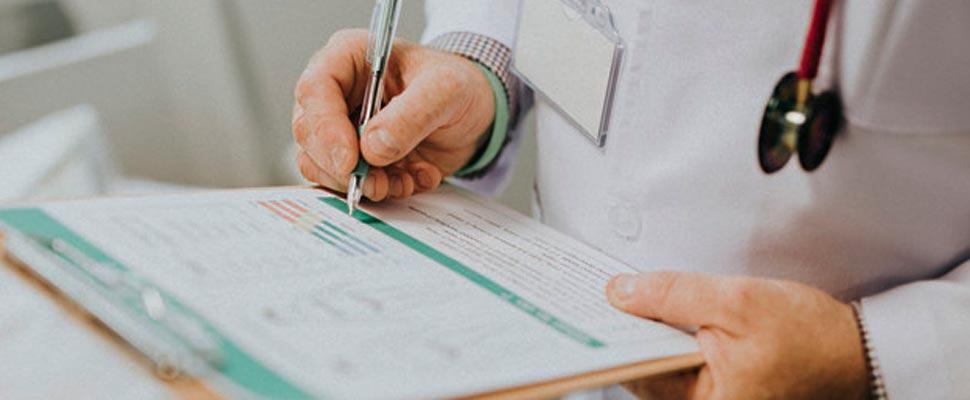 Doctor tomando notas en la historia clínica