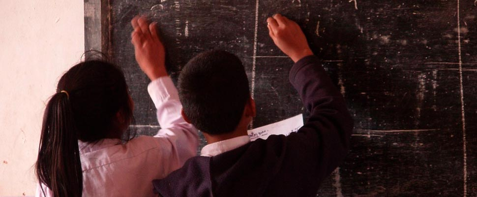 Two students writing on a board