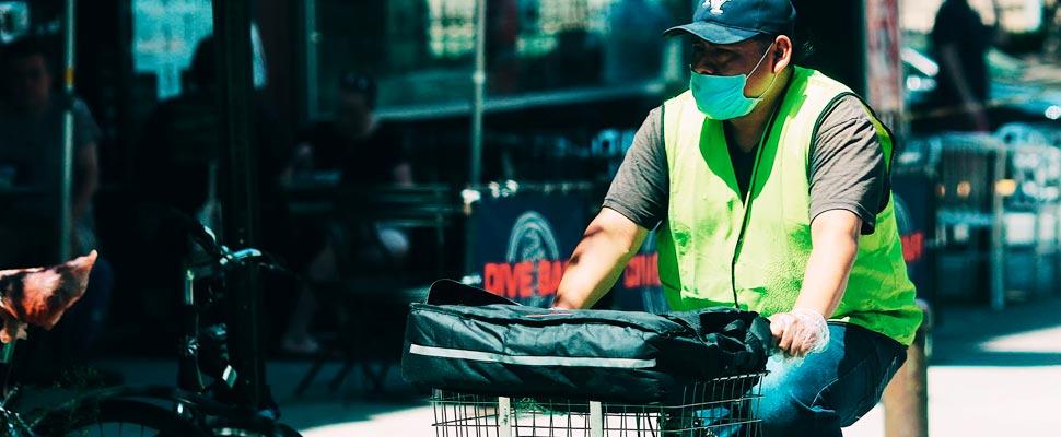 Hombre montado en bicicleta con una máscara