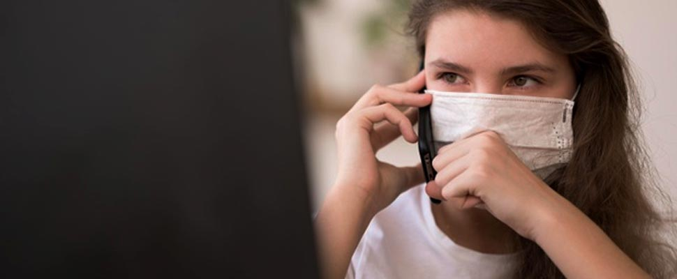 Chica con una máscara y hablando por teléfono