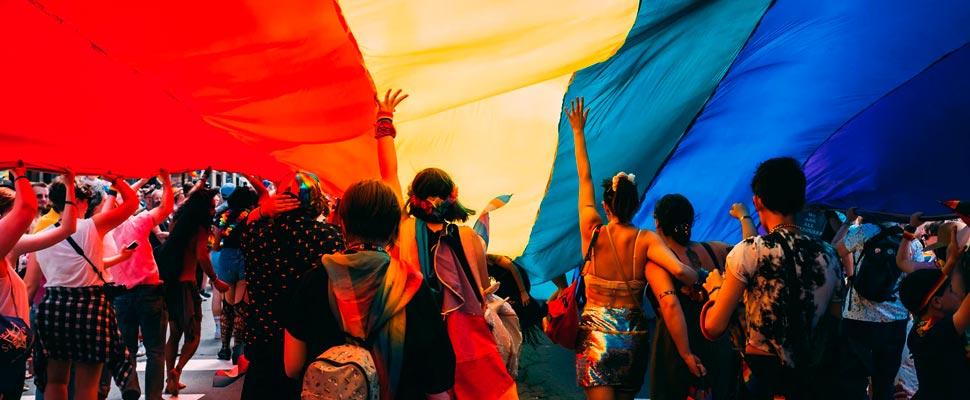 Grupo de personas marchando bajo una bandera LGBTI