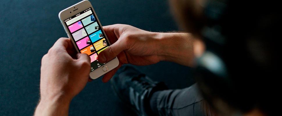 Hombre escuchando música en su celular en la aplicación de Spotify