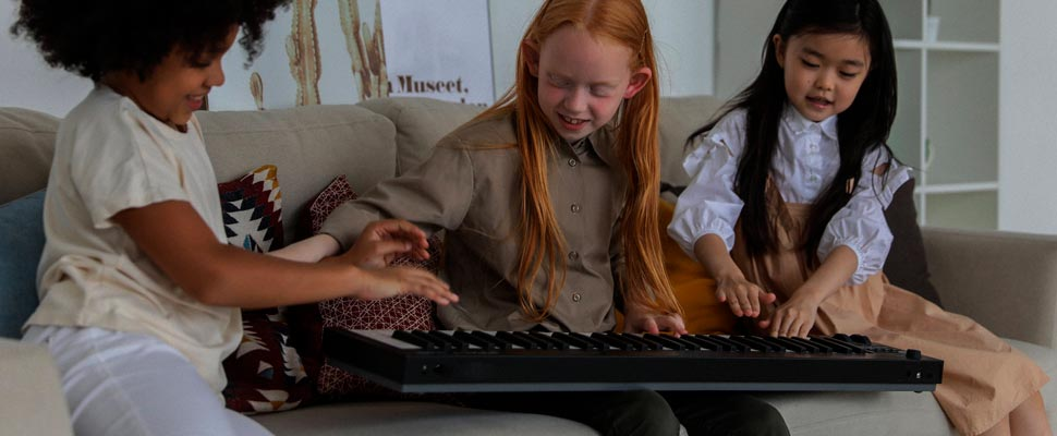 Three girls playing synthesizer