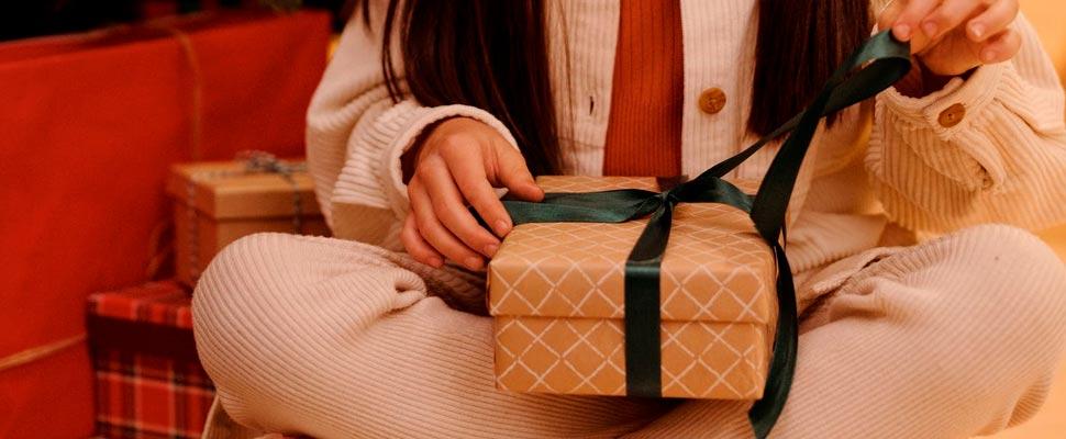 Niña abriendo un regalo de navidad