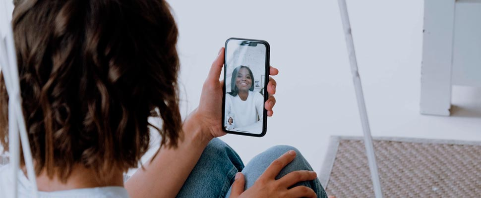 Two people holding their phones during a video call