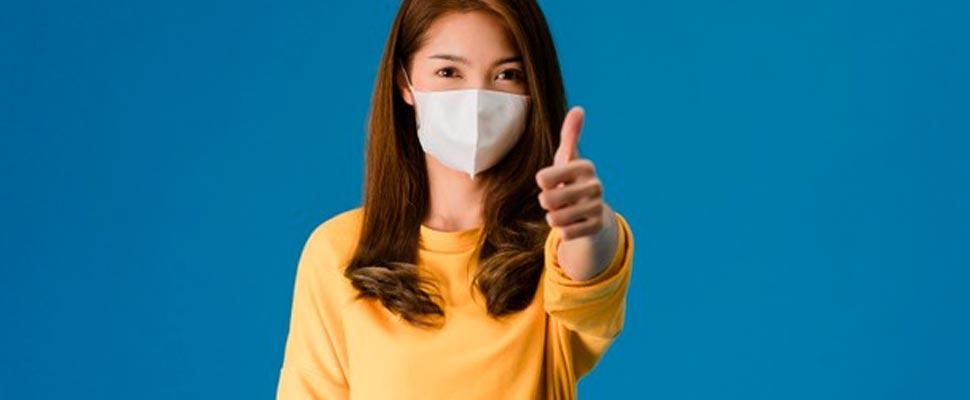 Woman wearing mask showing thumb up