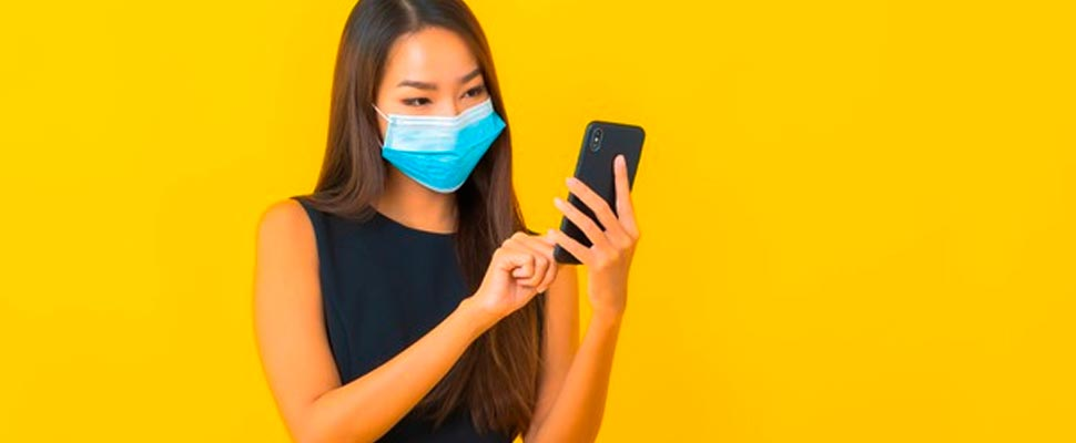 Mujer usando un cubrebocas y sosteniendo un celular