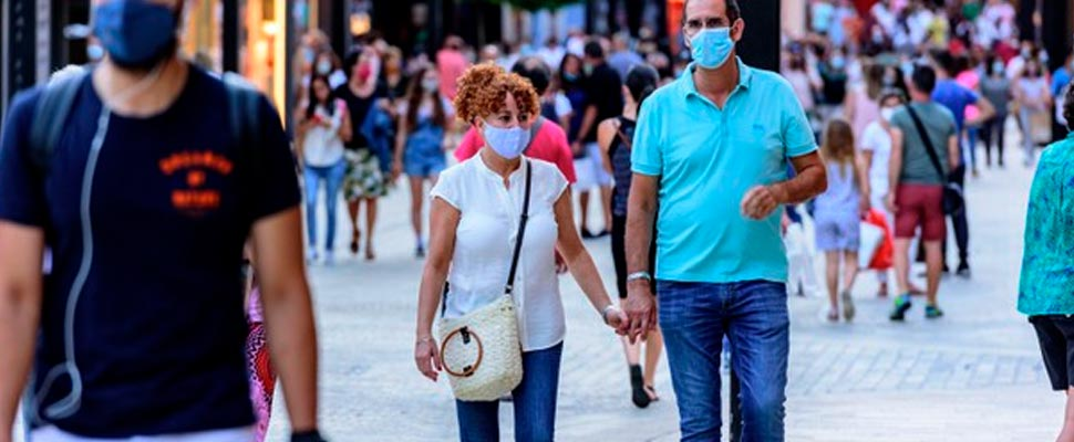 People walking down the street wearing face masks