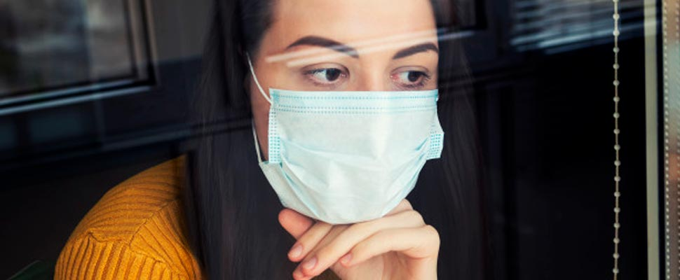 Woman looking out a window wearing mask