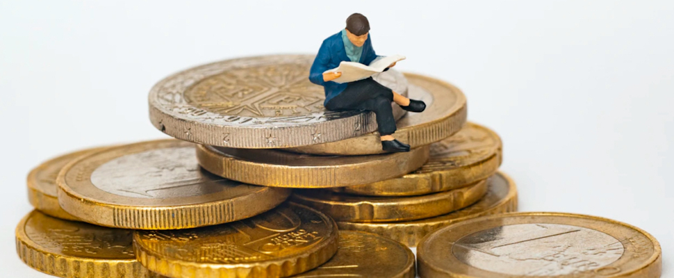Hombre sentado sobre monedas
