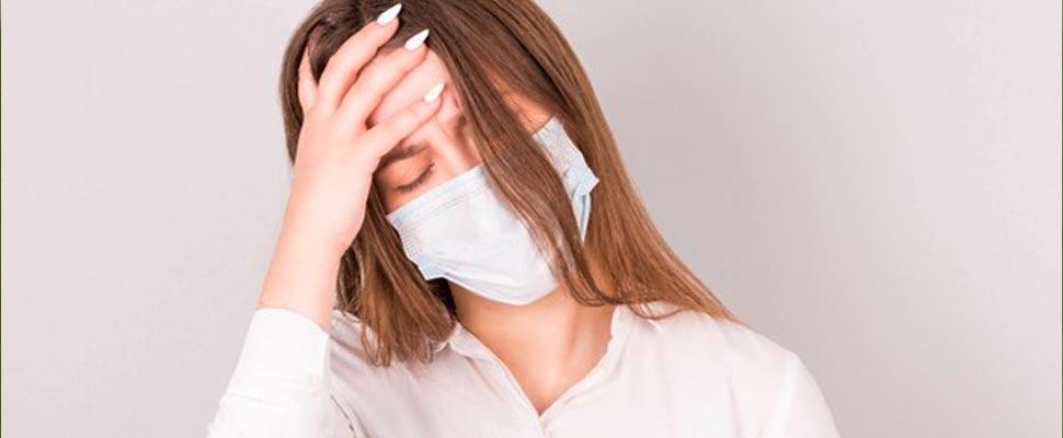 Mujer usando una máscara y tocando su cabeza