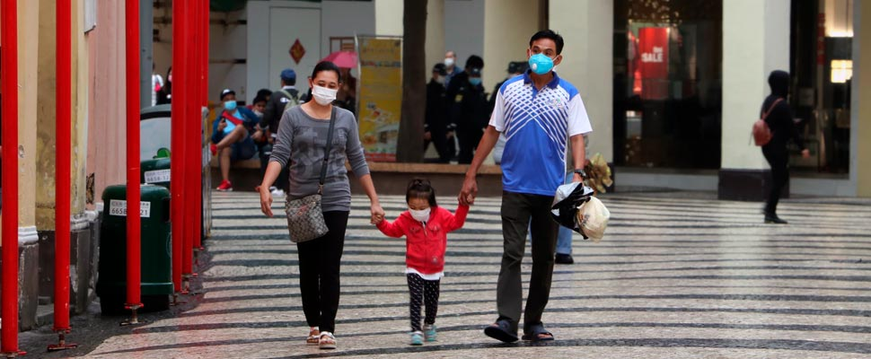 Family walking down the street wearing face masks