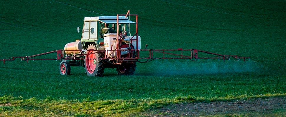 Machine spraying a field with glyphosate