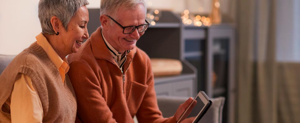 Dos personas mayores mirando una pantalla de iPad