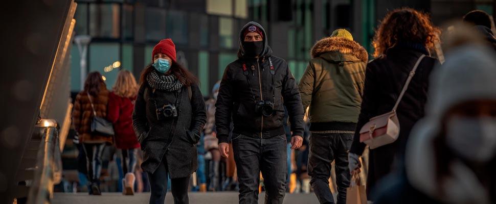 People walking in a street wearing face masks