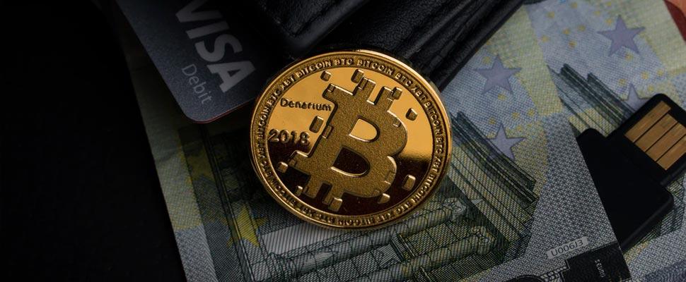 Moneda de bitcoin sobre unos billetes y una tarjeta de crédito