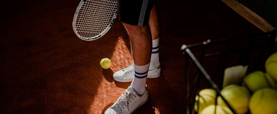 Piernas de hombre con una raqueta y pelotas de baseball