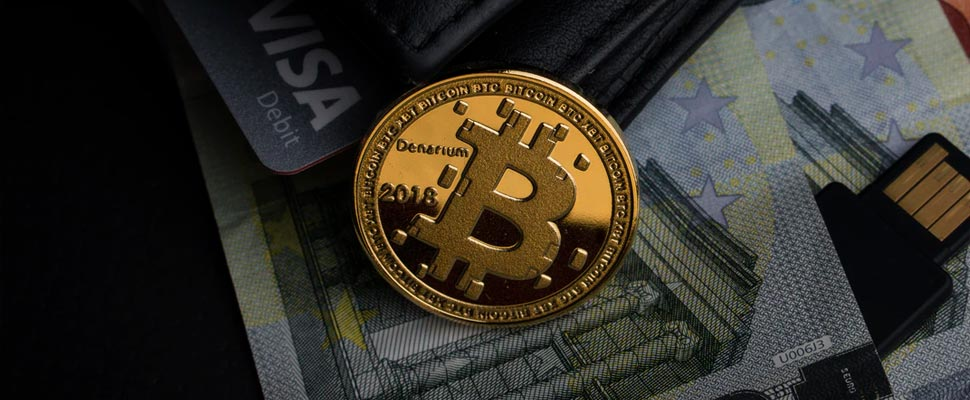 Bitcoin coin on some banknotes and a credit card