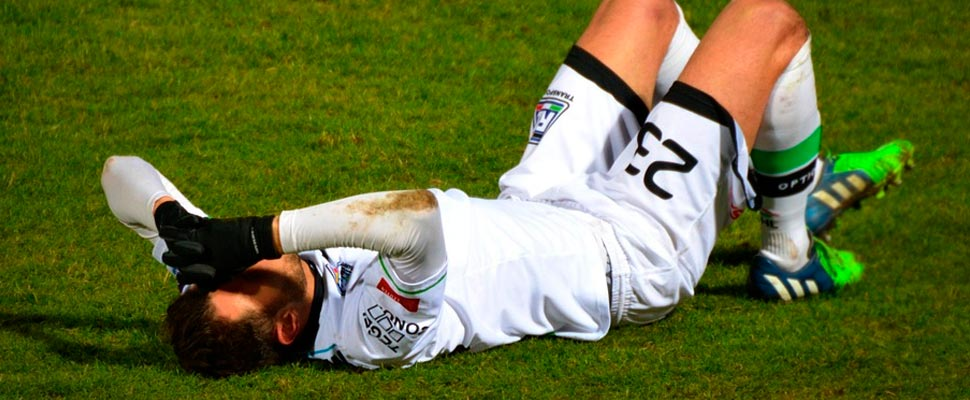 Footballer lying on the playing field