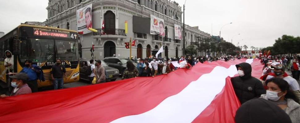 Peruanos marchando en las calles sosteniendo una bandera de Perú.