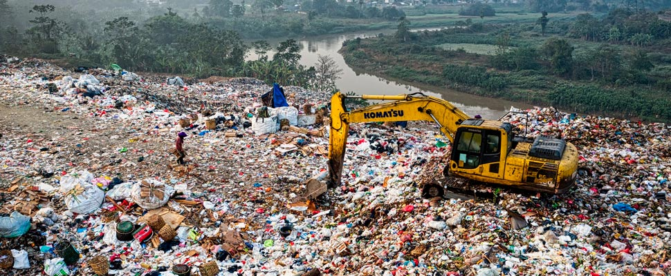 Excavator on a mountain of garbage