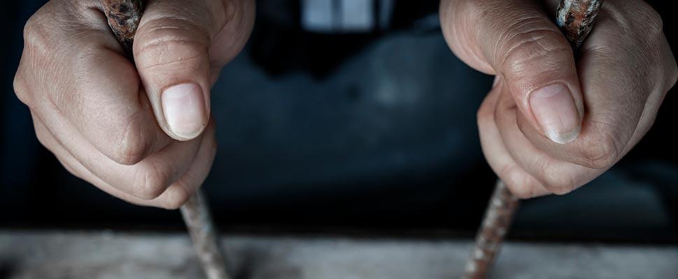 Hands of a prisoner in some bars