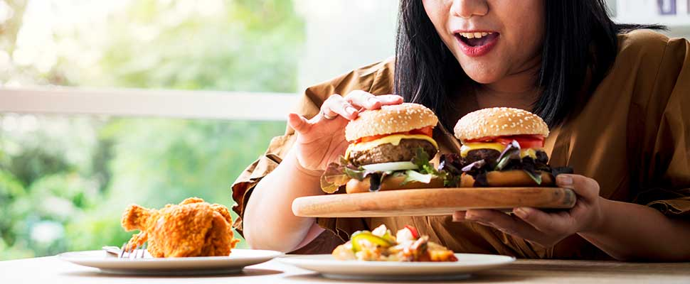 Hungry overweight woman holding hamburger on wooden plate