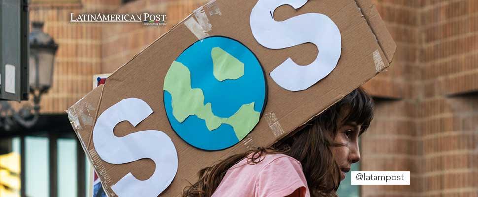 Activista sosteniendo un letrero de SOS al planeta