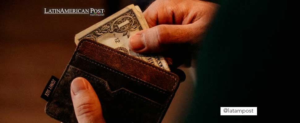 Persona guardando un dolar en su billetera