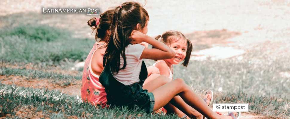Niños sentados en el pasto