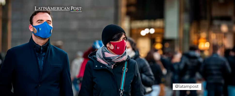 Couple walking down a street while wearing face masks