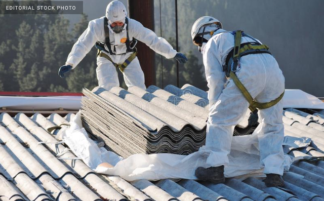 Workers handling tiles made of asbestos.