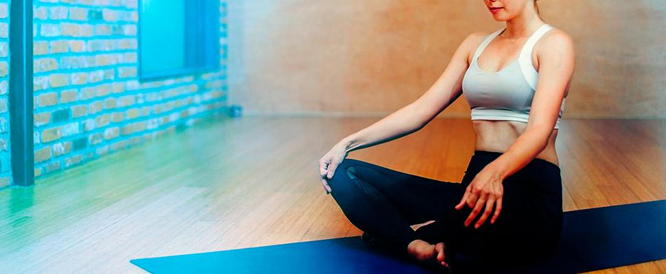 Mujer practicando gimnasia abodminal hipopresiva sobre colchoneta y usando ropa deportiva