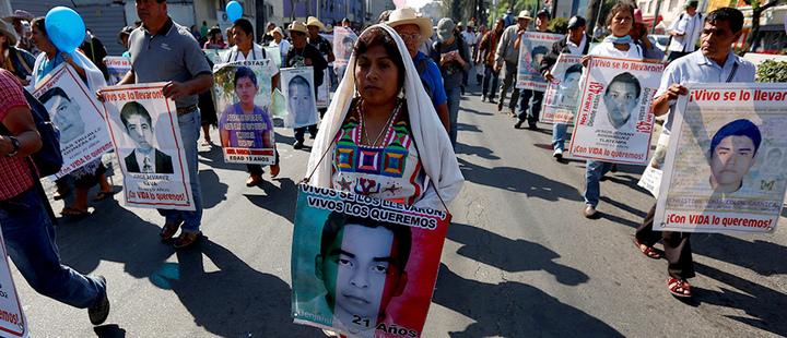 Manifestantes sosteniendo fotografías de los 43 estudiantes desaparecidos en Ayotzinapa
