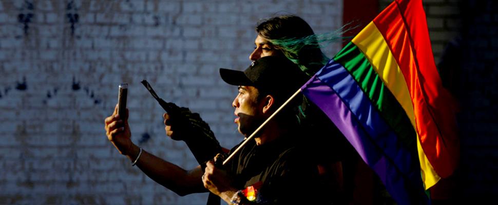 Pareja caminando y sosteniendo la bandera LGBT
