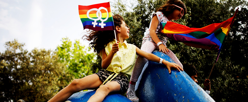 Two girls playing in a park and holding LGBT flags