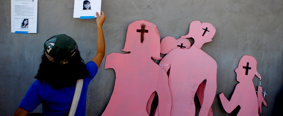 figuras de cartón con forma de mujeres y mujer colgando afiches en la pared