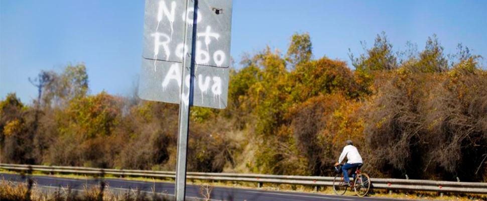 Hombre paseando en bicicleta por una carretera y aviso de 'No más robo de agua' en la vía